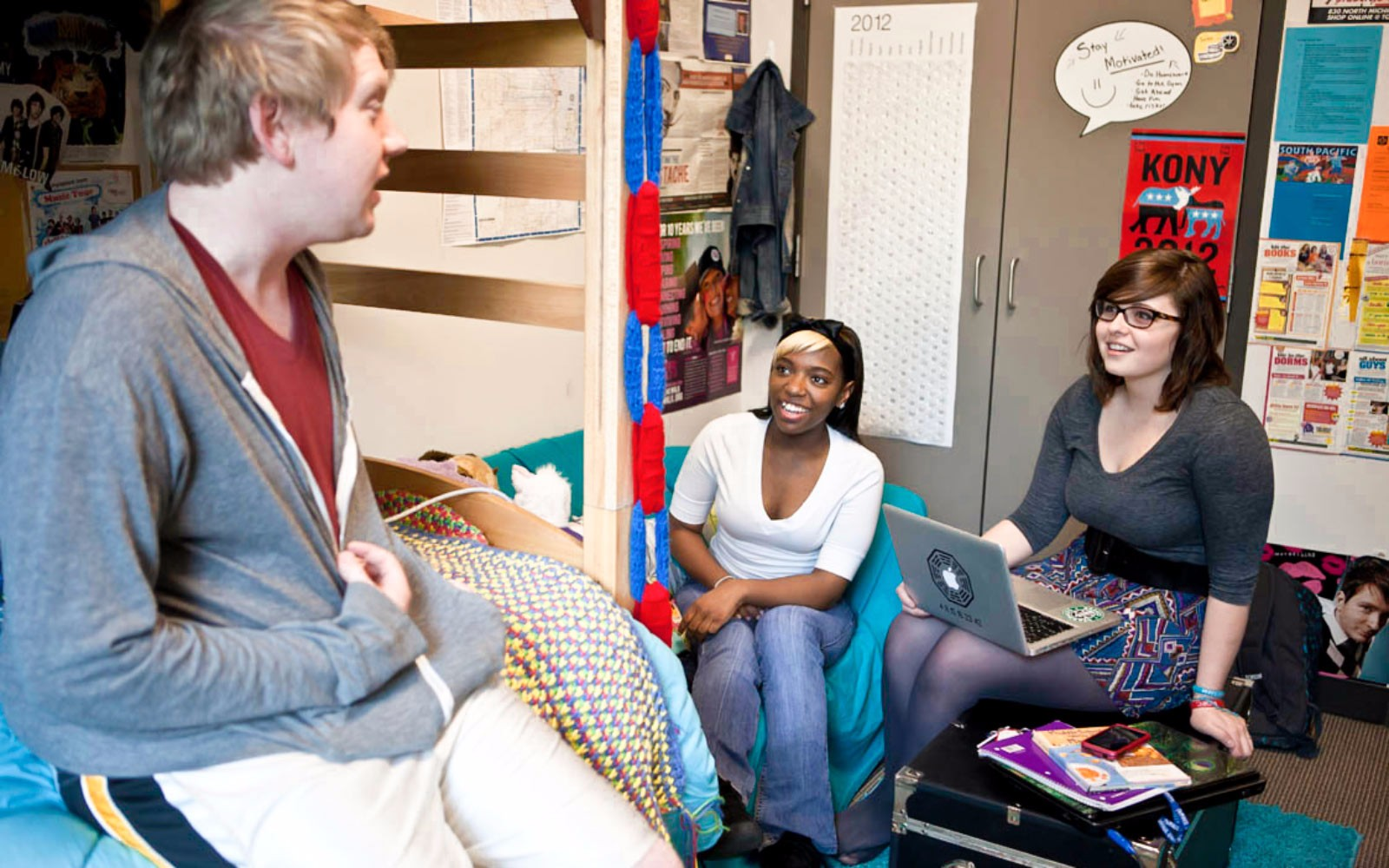 Three students laughing in a dorm room.