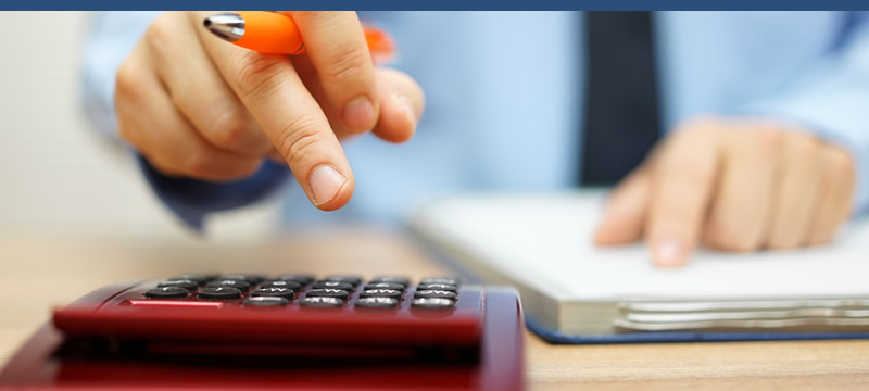 Man in business clothes sitting at a desk using a calculator