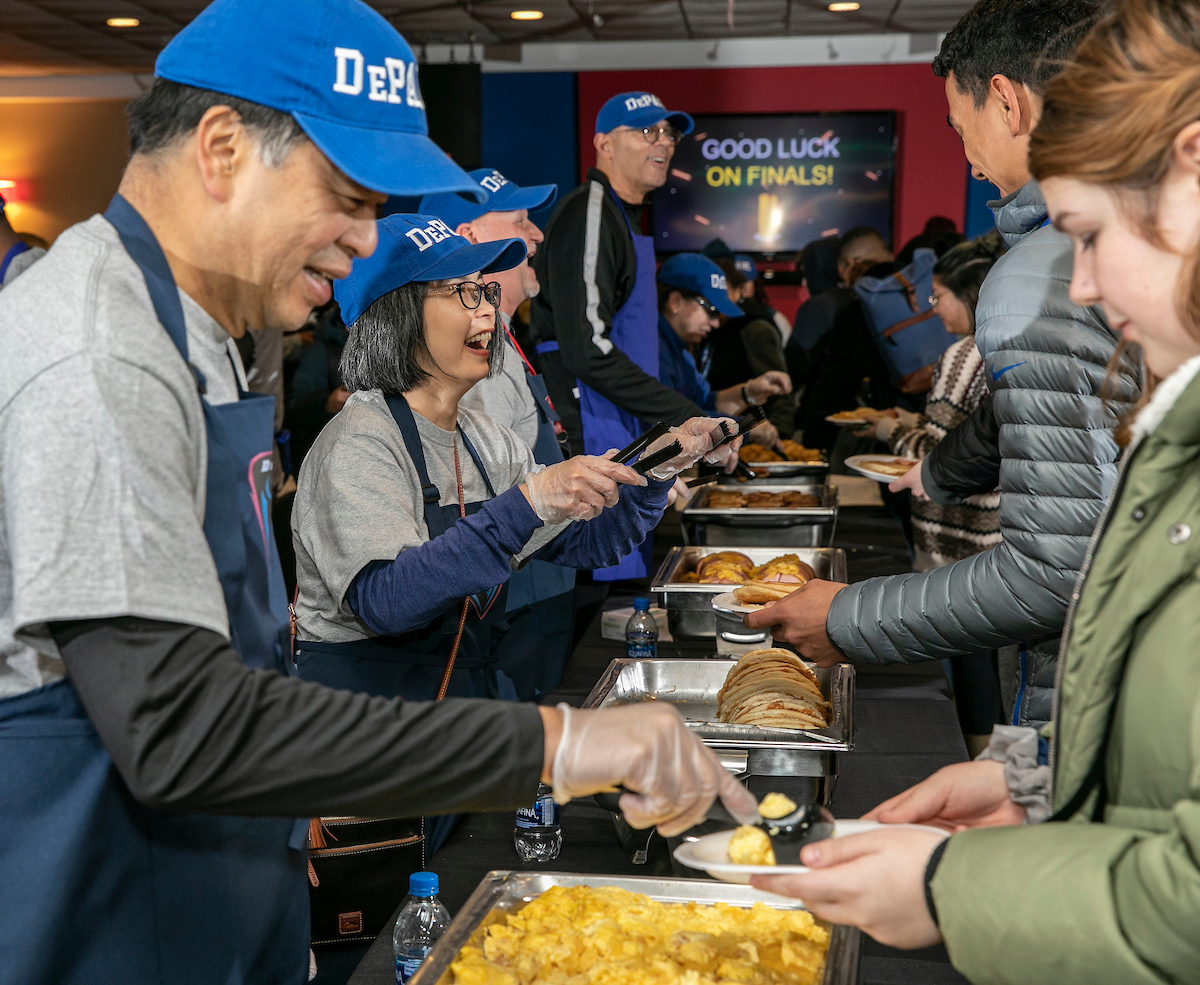 A. Gabriel Esteban, Ph.D., president of DePaul, his wife, Josephine, serve breakfast to study-weary students during the second annual Midnight Breakfast. (DePaul University/Jamie Moncrief)