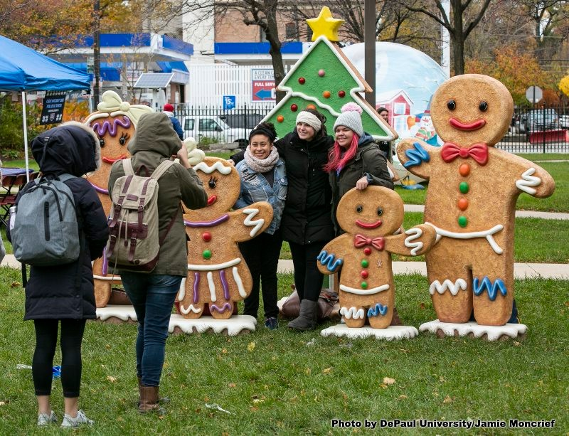 Students take picture near large gingerbread men